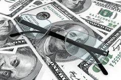 Metal los vidrios de lectura con el dinero. Imagenes de archivo