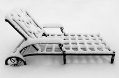 Metal Lounge Chair in the Snow. A metal lounge chair covered in snow, concept or metaphor for a harsh winter season.  If this doesn`t make you cold, I don`t know Royalty Free Stock Photography