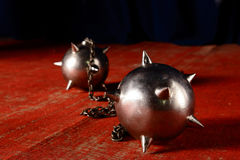 Metal maces on a chain laying on old red carpet Stock Images