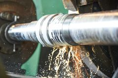 Metal industry. finishing shaft surface on grinder machine. Metal machining industry. finishing or grinding shaft surface on grinder machine at factory royalty free stock photography