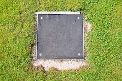 Metal manhole cover drainage system in the midst of cropped grass Stock Image
