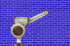 Metal meat grinder on blue brick wall background. Royalty Free Stock Images