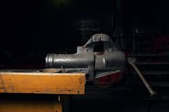 Metal mechanical vice mounted on a wooden workbench in the repair shop.  stock image