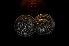 Metal medals inspired by the Stark house shields and Targaryen from the TV series Game of Thrones for sale as amulets. Caceres, Extremadura, Spain - March 13 royalty free stock photo
