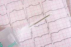 Metal medical needles on the background paper ECG Royalty Free Stock Image