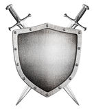 Metal medieval shield and crossed swords behind it isolated Stock Photo