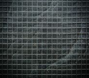 Metal mesh on black stone wall background in the dark.  Stock Photo