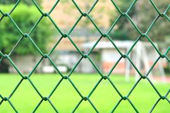 Metal mesh with blur soccer field background Stock Photography