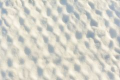 A metal mesh covered with a thick layer of snow. The texture of the snow. Unusual background. A metal mesh covered with a thick layer of snow in the cells. The Stock Images