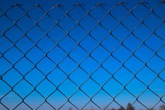 Metal mesh fence against a blue sky. Metal grid through which the object is visible royalty free stock photos