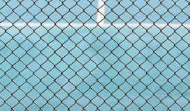 Metal Mesh fence on blurred background of blue tennis hard court Stock Photos