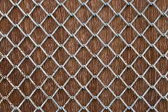 Metal mesh grid on plank wood. Royalty Free Stock Image