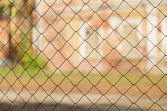 Metal mesh netting on the background of blurred buildings Royalty Free Stock Photography
