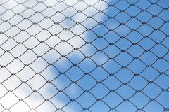 Metal mesh netting on the blue sky background and clouds Royalty Free Stock Images