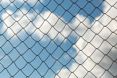 Metal mesh netting on the blue sky background and clouds Stock Images