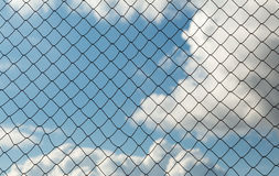 Metal mesh netting on the blue sky background and clouds Stock Photo