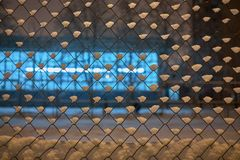 Metal mesh with snow before night club in winter in frost at evening. stock image