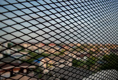 Metal mesh with town in the background. Seeing town throung the metal mesh Stock Photography