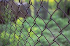 Old steel wire mesh fence with blurred green background close up. Metal mesh is used for fencing real estate and sports grounds royalty free stock images