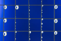 Metal mesh with water drops on the blue background Royalty Free Stock Photos