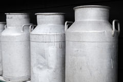 Metal milk churns stand in a row, close up Stock Photos