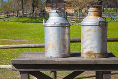 Metal milk churns stand on wooden table Stock Photo
