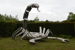 Metal model of big white scorpion. Photo of metal model of big white scorpion in park, green trees and grass, cloudy sky royalty free stock image