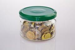 Metal moedas em um frasco de vidro com uma tampa em um fundo branco Fotografia de Stock Royalty Free