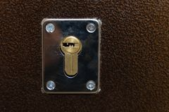 Metal mortise lock without a key in the brown metal entrance doors royalty free stock image