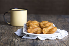 Metal mug full of coffee and a plate of koeksisters on brown woo Royalty Free Stock Photos