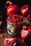 Metal mug full of pomegranate seeds royalty free stock image