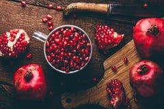 Metal mug full of pomegranate seeds stock image