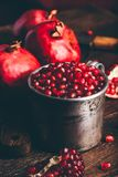 Metal mug full of the pomegranate seeds stock photography