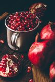 Metal mug full of pomegranate seeds. Whole fruits and pomegranate pieces on dark wooden surface stock photography