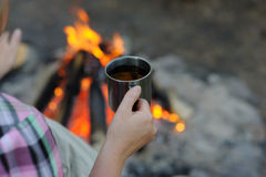 Metal mug in the hands of a tourist, in the woods near the fire. Royalty Free Stock Images