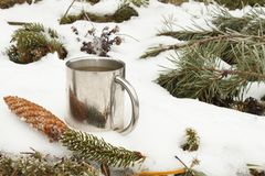 Metal mug of hot tea in snow. Hot drink on a frosty day Stock Image