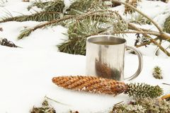 Metal mug of hot tea in snow. Hot drink on a frosty day Stock Images