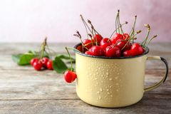 Metal mug with ripe red cherries. On wooden table Royalty Free Stock Image