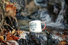 Metal mug on rocks outdoors