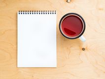Metal mug with tea, empty a blank sheet of notepad on the spiral Stock Photo