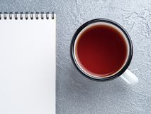 Metal mug with tea, empty a blank sheet of Notepad on the spiral Stock Photography