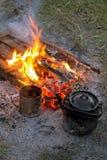 Metal mug and teapot near the campfire Stock Photography