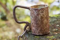 Metal mug for water with a chain near to source. Stock Photos