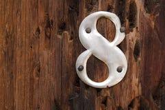 Metal número 8 no fundo de madeira Fotos de Stock