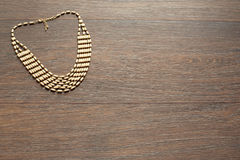 Metal necklace for women on brown wooden background. The view from the top. The concept of beauty, fashion and design stock photo