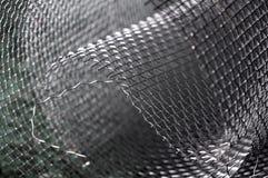 Metal net closeup. Rolled and wavy metal net closeup Stock Photos