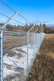 Metal net fence with barbed wire Stock Photography
