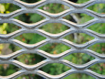 Metal net with green blured background. Royalty Free Stock Photo