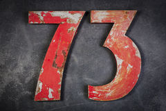 Metal number seventy-three. Red metal number seventy-three on a the wall Stock Images