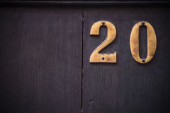 Metal number twenty with large dark wooden background Stock Photos